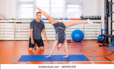 Girl doing a cartwheel exercise, showing gymnastic skills in a physical activity class