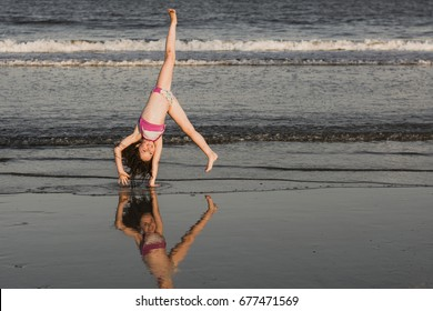 Girl doing cartwheel on beach