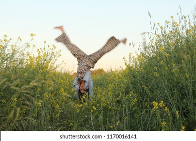 Girl doing cartwheel in tall grass and wild flowers.