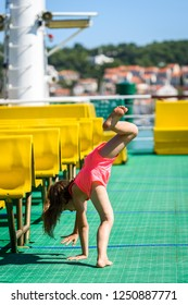 Girl doing cartwheels on Croatian ferryboat in Mali Losinj. Little girl is activly doing cartwheels on vacation. Concept of active children, fitness and healthy lifestyle.