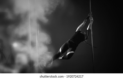 Girl doing exercises on a sports equipment. The dancer on the pylon in the studio.