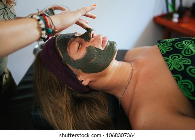 The girl doing the facial massage. The girl put a clay mask on the face. The cream on the face. Ayurvedic treatment. Spa treatments in Asia. Ayurveda salon