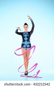 The girl doing gymnastics dance with colored ribbon on a blue background