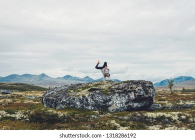 Girl doing handstand, breakdancing in beautiful scenic mountain landscape. Hip hop, dancing, handstand, freedom, woman, nature concept.