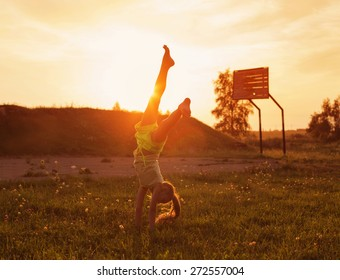 girl doing a handstand in a meadow