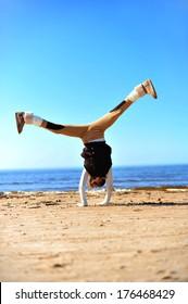Girl doing handstand on the sunny beach