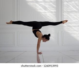 girl doing handstand and split in white studio