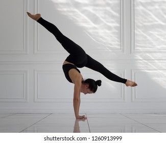 girl doing handstand and split in white studio