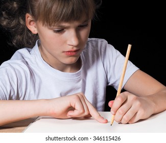 Girl doing homework. The girl is hard, it is difficult to perform the task. In the hands of a pencil. black Background