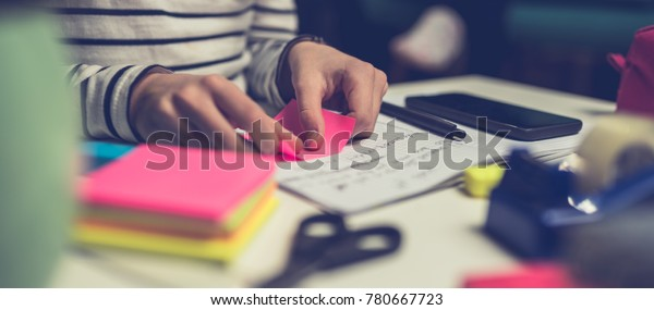 Girl doing homework late at night and peeling off sticky notes