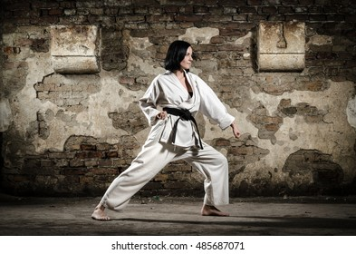 Girl doing karate exercise. Grunge wall background. Martial arts.