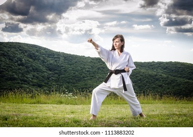 Girl doing karate exercise outdoors. Martial arts.