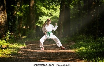 A girl is doing karate in nature.