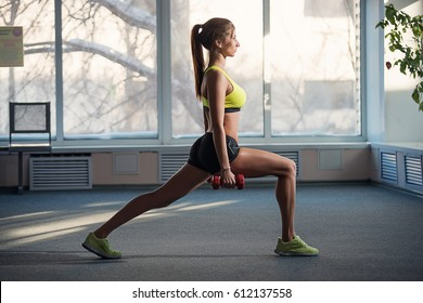 girl doing lunges with dumbbells in the gym