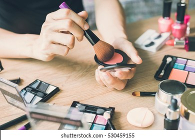 Girl doing makeup on dressing table with cosmetics