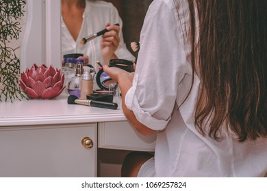 Girl doing make-up sitting at dressing table with decorative cosmetics. Home interior.
