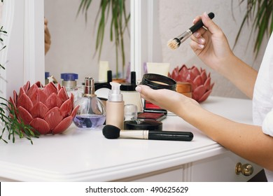 Girl doing makeup sitting at dressing table with decorative cosmetics. Home interior.