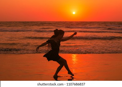 The girl is doing the movements at the seaside. Feeling light and elegant dancing, orange lights illuminates her silhouette.