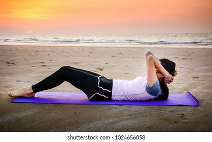 Girl doing situps on the beach at sunset, outdoors workout