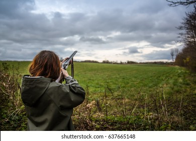 Girl doing skeet shooting outside on a field.