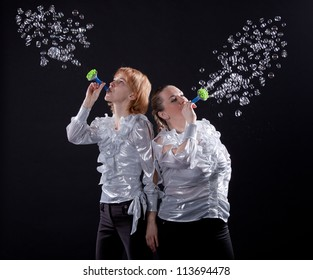 girl is doing soap bubble show on the black background