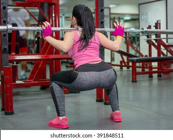 Girl doing squats with a bar at the gym