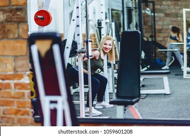 girl is doing squats in simulator at gym