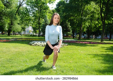Girl doing stretching leg outdoors in the park against the backdrop of greenery