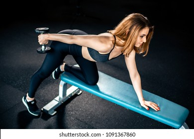 Girl doing triceps exercise with dumbbells in gym