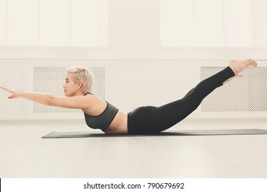 Girl doing warming up exercise for spine, backbend, arching stretching her back working out at yoga class, copy space