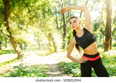 Girl doing warmup exercise at the park. Young woman stretching before running. Female fitness model working out outdoor. Concept of healthy lifestyle.