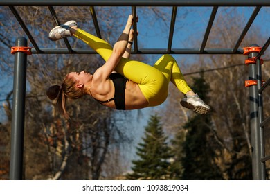 Girl doing workout. She makes stretching upside down on parallel pereklidinah. She is dressed in black top and yellow sports pants.