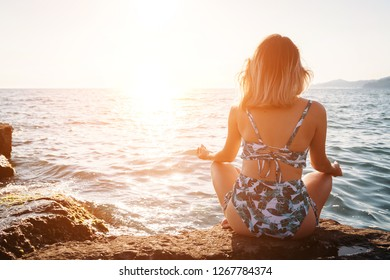 Girl doing yoga at the beach, at sunset time. Healthy lifestyle.