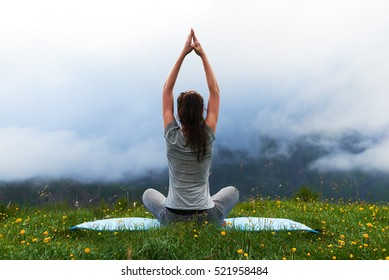 girl doing yoga exercise lotus pose on the lawn in the mountains