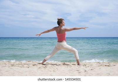 Girl doing yoga exercise on a beach in Sardinia