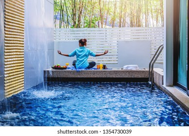 Girl doing yoga fitness exercise for relax and meditation at poolside Inside in the house,during meditation with a orange juice and fruit, apples, oranges placed on the side.