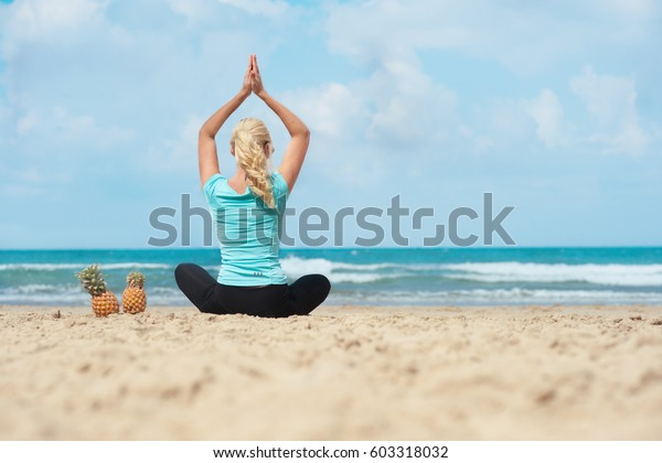 girl doing yoga and health lifestyle with fresh pineapples fitness exercises warm summer ocean beach with holiday mood and vacation healthy lifestyle  in Kibbutz in Israel or Ashram in India or camp