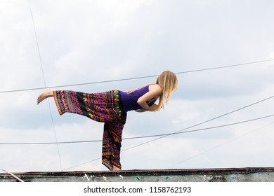 Girl doing yoga on the roof of the building