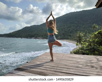 Girl doing yoga on a rooftop with a beautiful view to the beach on a tropical island in Thailand