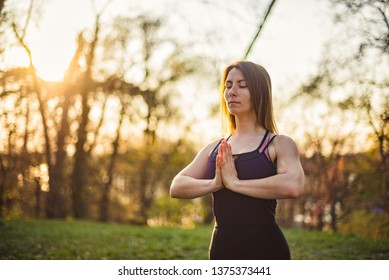 Girl doing yoga in park, relaxing and meditating while being surrounded by nature.