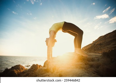 girl is doing yoga, standing in bridge pose ( Setu Bandhasana ) on rocks by the sea with sunset on background