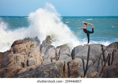 girl is doing yoga, standing in Lord of the Dance pose (Natarajasana) on rocks near crashing wave