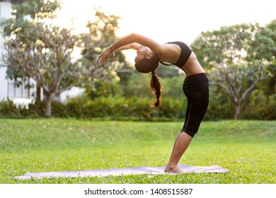 girl doing yoga at sunset in Thailand in the park