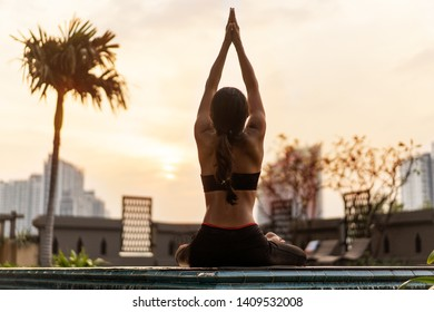 girl doing yoga at sunset in Thailand near the pool