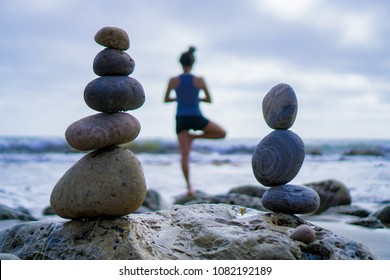 Girl doing yoga tree pose in front of stacking rocks