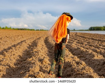 Girl doll with red hair, hat, black T-shirt, green army pants and red boots walking in a plowed field.