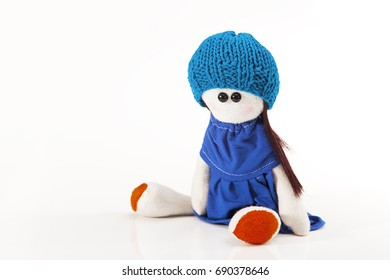 Girl doll sitting with dress and knit hat, in white background