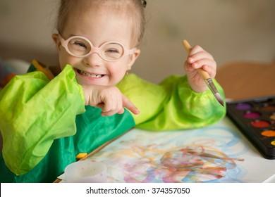 Menina com síndrome de Down desenha tintas