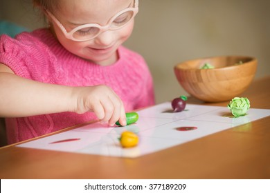 Girl with Down syndrome with interest sorting vegetables