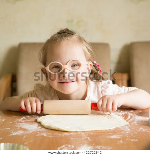 girl with down syndrome unrolls dough